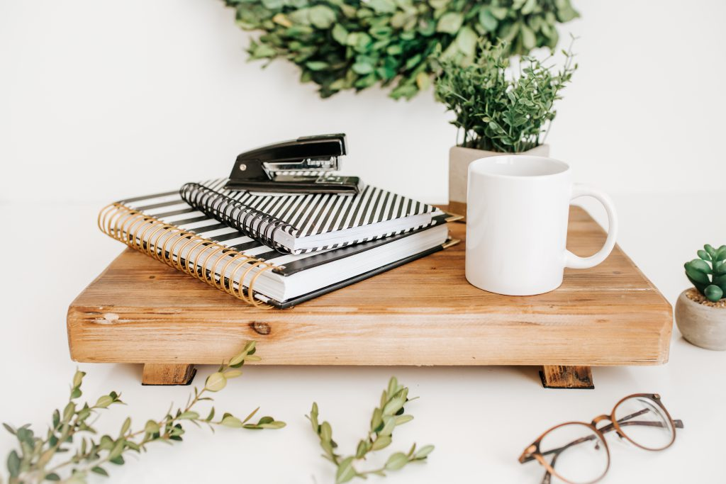 Greenery with office supplies, mug, glasses, stapler, notebook
